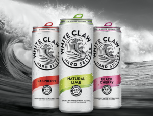 Three cans of White Claw Hard Seltzer against an image of a wave